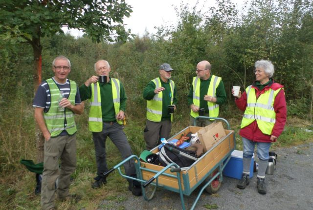 Group of five volunteers gathered around a wheel barrow full of tools, having a tea break