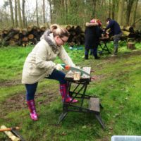 Participant cutting wood with hand saw in woodland