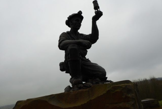 Statue of a miner holding up a mining lamp