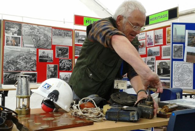 A member of the group demonstrating how some mining equipment works as part of a community event