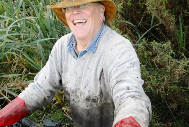 A man in a hat, up to his waste clearing a pond. Looking very happy.