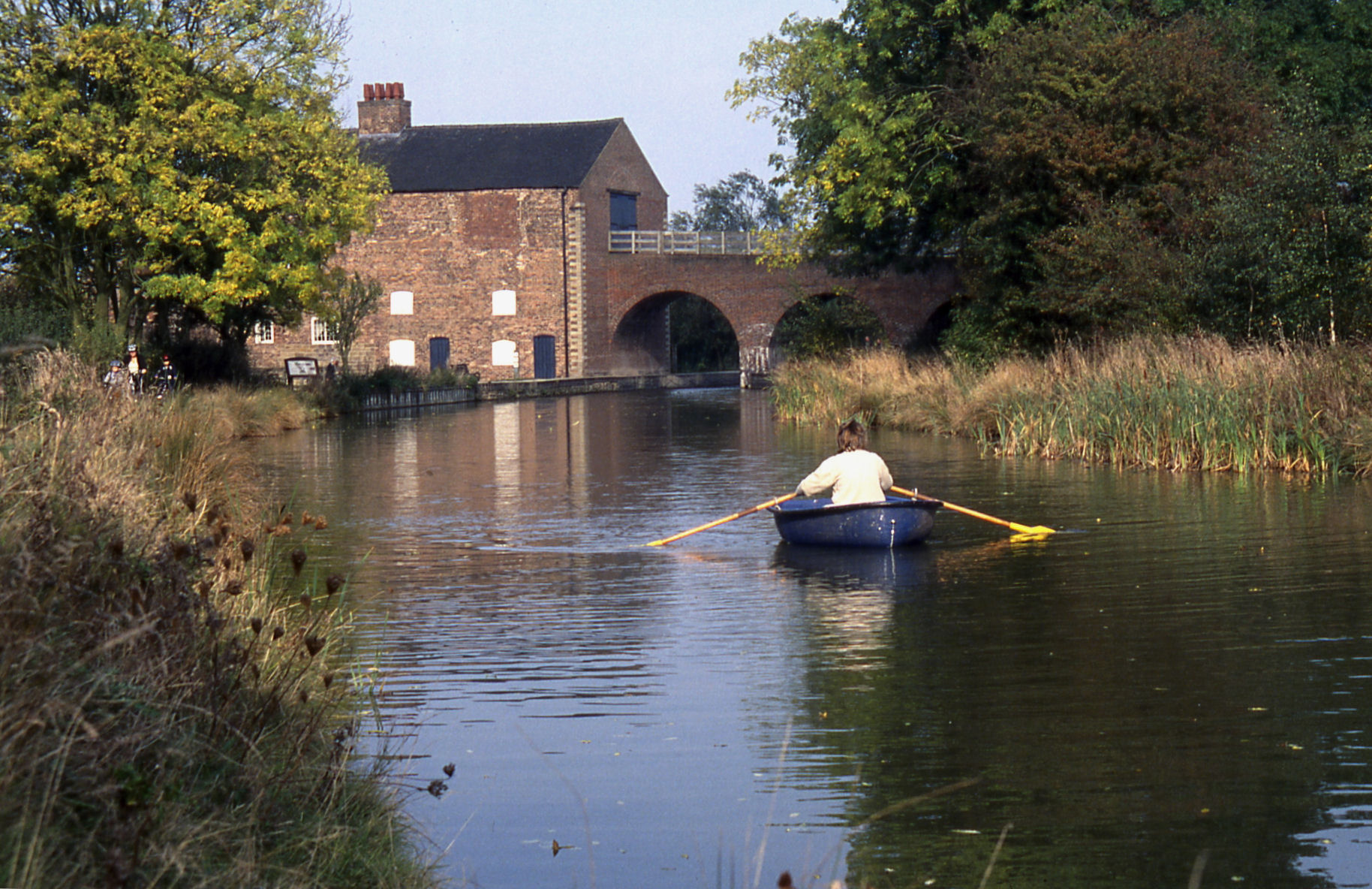 Small rowing boat on Ashby Canal, with Moira Furnace in the background