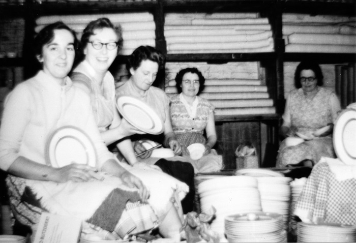 Black and white photo of a group of 4 seated ladies from TG Green testing for cracks in plates