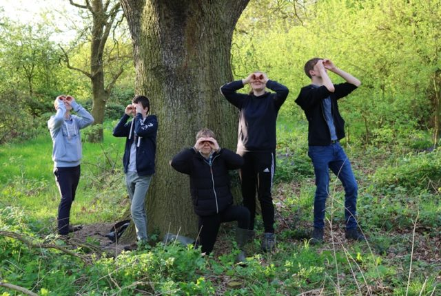 Five young people stood round a tree with their hands held up to their eyes in the shape of binoculars.