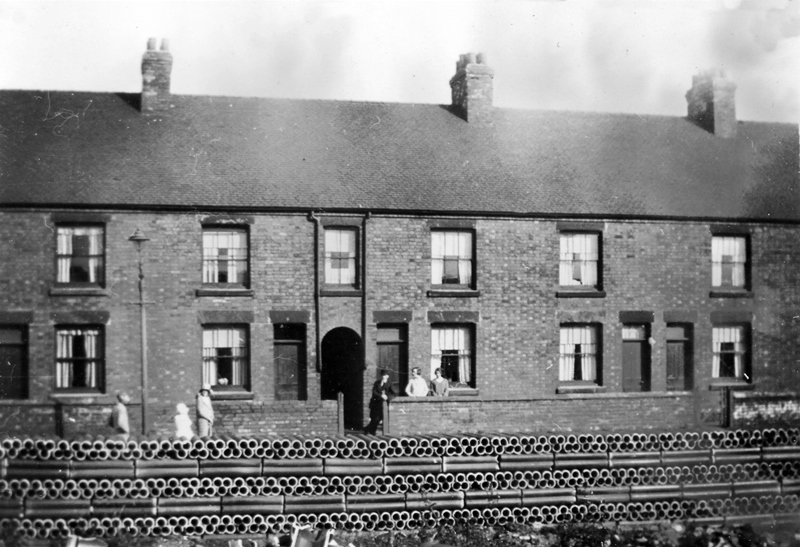 Black and white photograph of a row of terrace houses at Spring Cottage with a wall of pipes in front